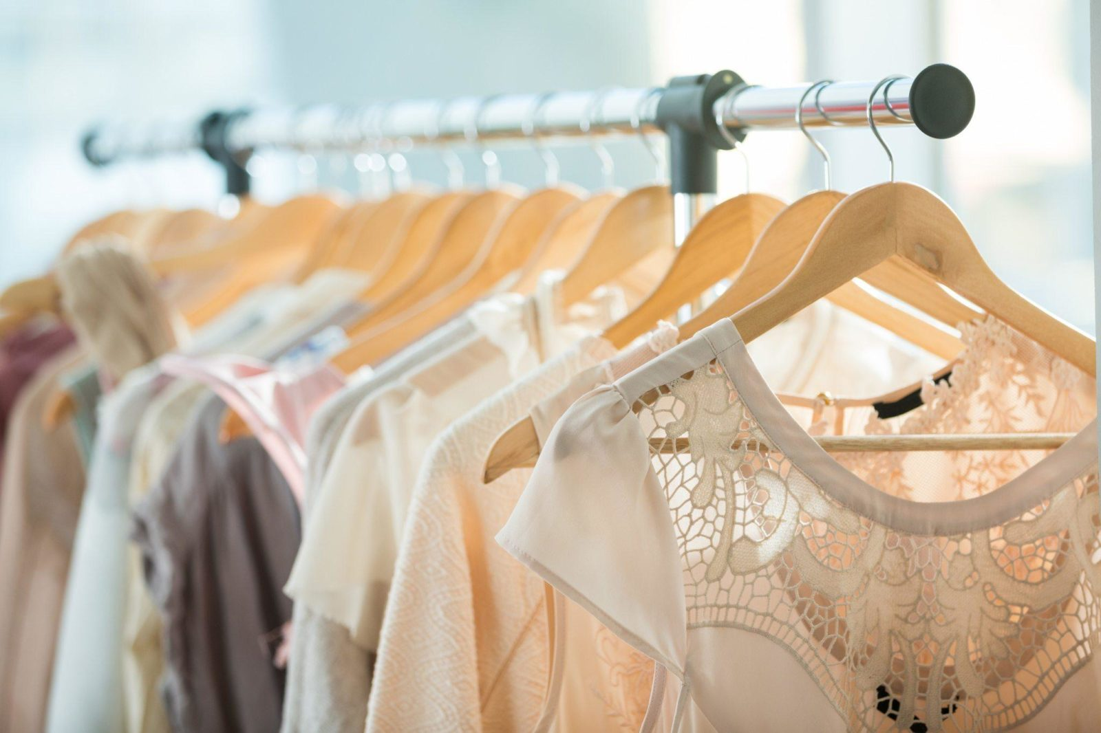 Set of light colored dresses on a wooden hangers