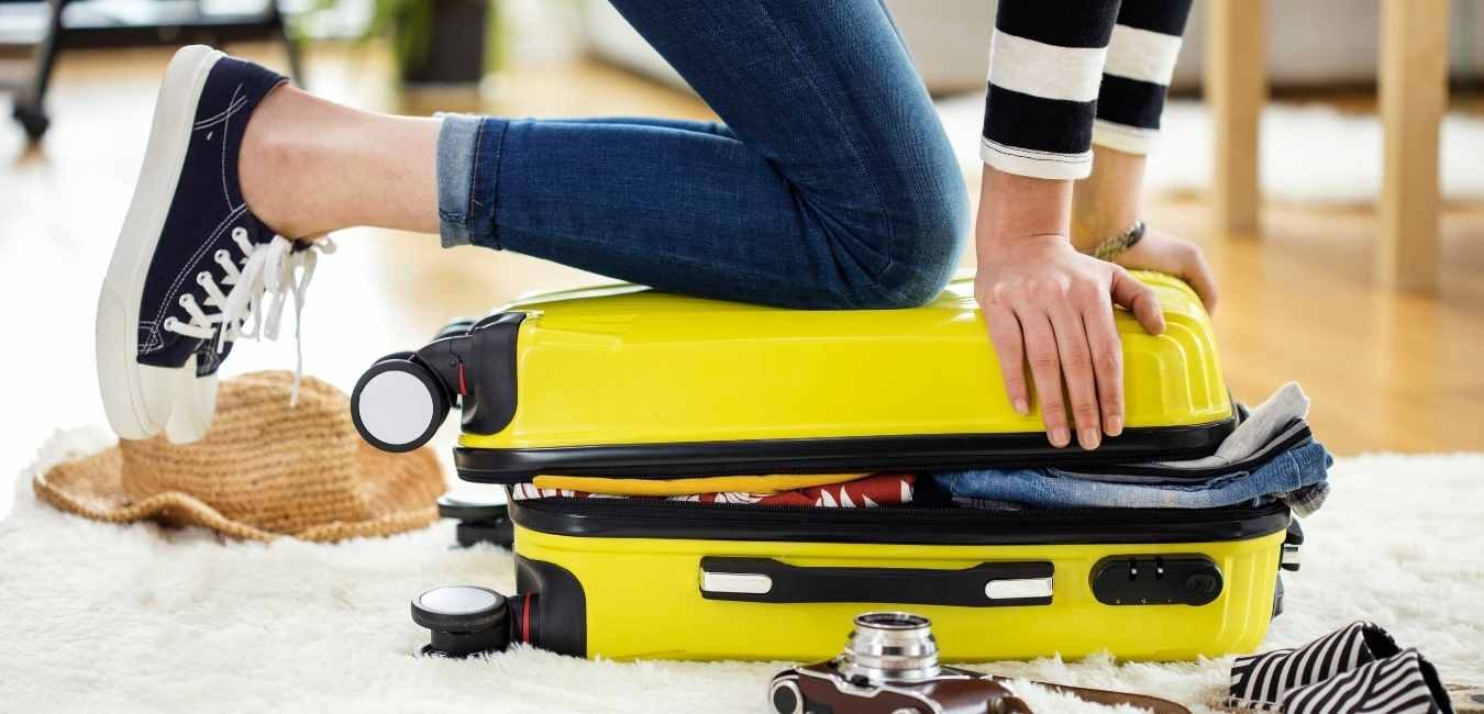 woman trying to close a suitcase Mexico travel tips